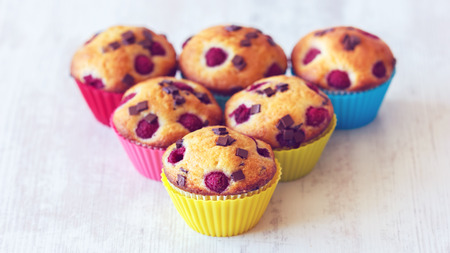 Group of delicious colored muffins placed on wooden white table. Muffins are very popular especially in the United States of America. photo