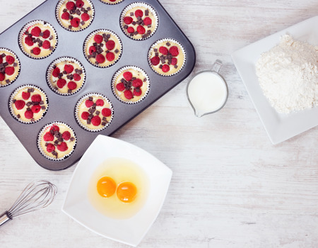 Top view of unripe muffins with ingredients. Two yolks, flour and milk placed on wooden white table. Space for text in the lower right corner. photo