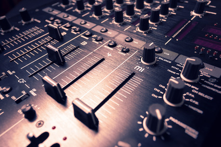 Wide angle photo of black sound mixer controller with knobs and sliders photo