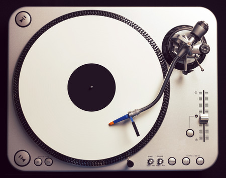 Old fashioned turntable playing a track from white vinyl. Shot from above, vintage cross processing. photo