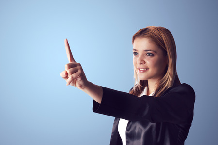 Smiling business woman pointing to empty space on the left side of the photo. Blue background. photo