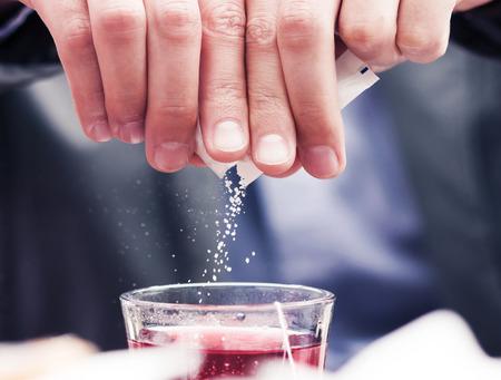 Close-up der weißen Zuckerpartikel fallen in Tasse mit Tee gefüllt.