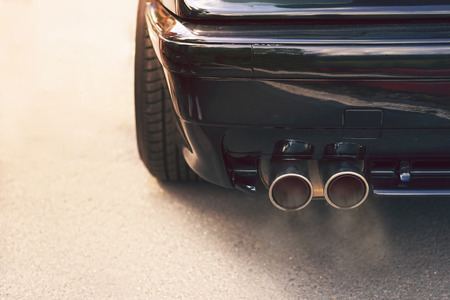 Close-up of black car dual exhaust pipe with smoke Imagens