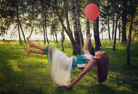 levitating: Beautiful woman with long dress levitating in forest while holding a red balloon. Cross processed image.