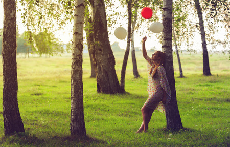 transparent dress: Woman playing with three balloons in park wearing transparent dress.