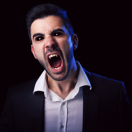 Scary man in suit with black eyes and fangs screaming against black background.