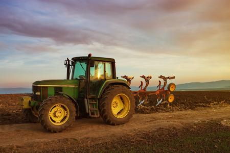 緑のトラクター耕起後のサンセットでのフィールドで 写真素材