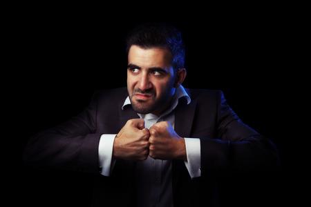 venganza: Hombre de negocios cauc�sico en el ejemplo de estar enojado, pensando en la venganza contra el fondo negro Foto de archivo