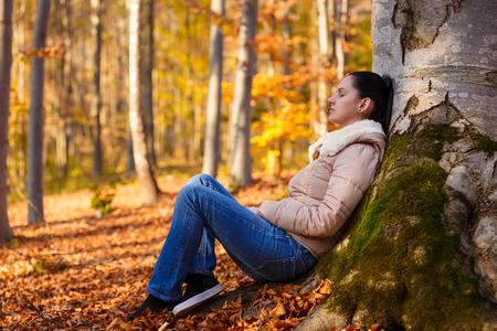 秋のシーズン中の仕事で長い日後の自然の中でリラックスした女性