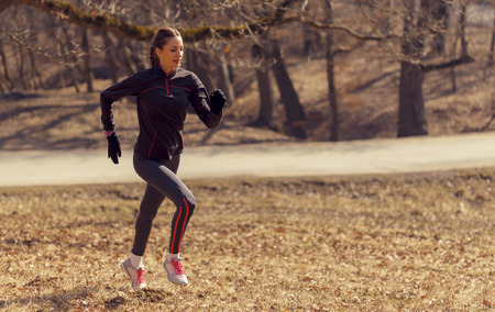 motivated: Woman running in the morning in nature while being positive and motivated
