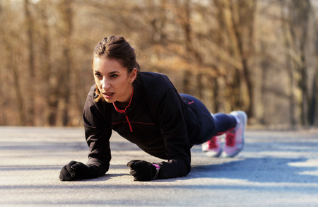 staying in shape: Sporty woman exercising in the morning outdoor.