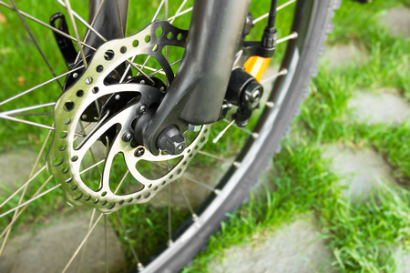 Disc brake detail on bicycle with grass in background.