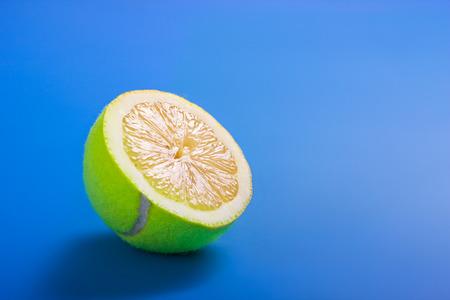 limón: Concepto de vida sana con la pelota de tenis en rodajas y lim�n sobre fondo azul Foto de archivo