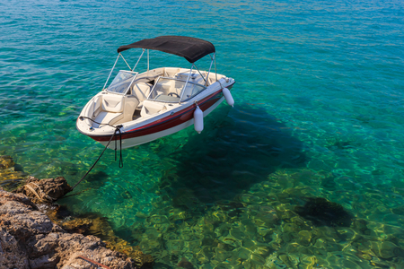 clear water: Small white boat floating in clean water near shore on a sunny day