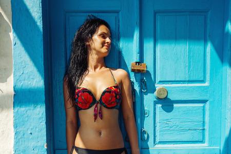 blue door: Happy woman posing in swimsuit against vintage blue door. Vintage effect.