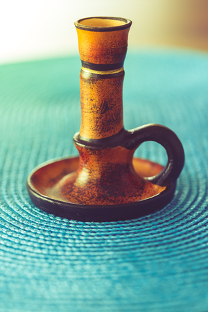 candleholder: Brown candleholder on blue tablecloth with copy space. Vintage effect. Stock Photo