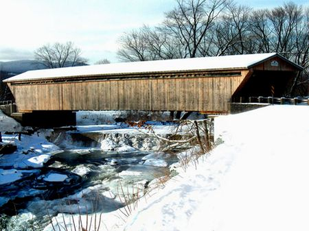 covered bridge': snow covered Long wooden covered bridge over partially frozen waterfall