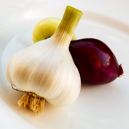 frugal: Homegrown, organic, onions harvested and put on White plate Stock Photo