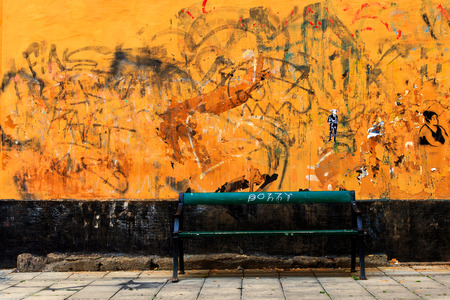 Orange wall covered in old graffiti and tags with a bench in front of it.