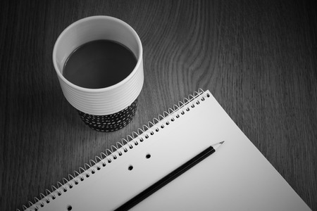 Coffee with milk in coffee cup by white paper and pencil on desk in black and white photo