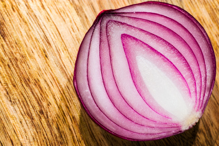 Close-up macro of red onion on wooden board Stock Photo