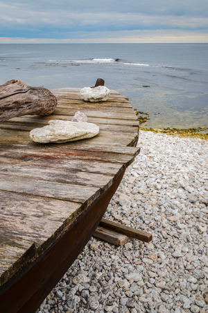 Skiff boat on stone beach by the ocean with stones on boat cover