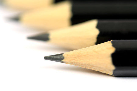 Macro close-up image of black pencils on white background with selective focus  shallow depth of field