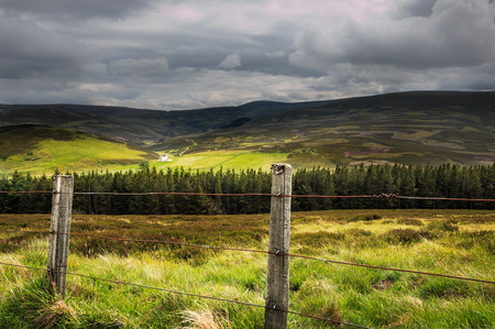 View of Scottish Highlands landscape in Scotland with fence in foreground