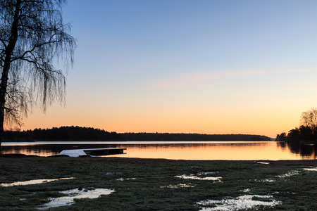 Swedish landscape with jetty, water and beach during dawn sunrise