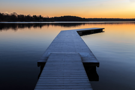 Swedish landscape with jetty and water during dawn sunrise