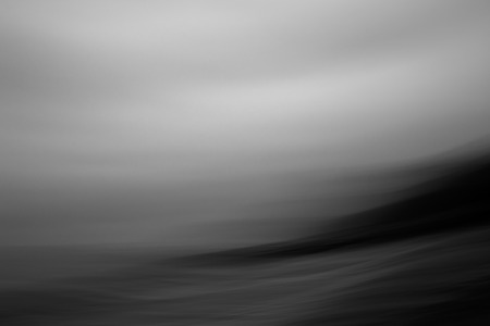 Abstract black and White image of waves crashing in over shore