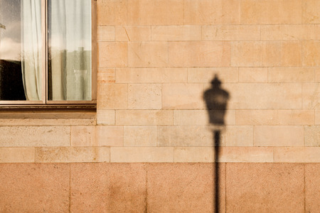 lamp post: Lamp post shadow on wall of house Stock Photo
