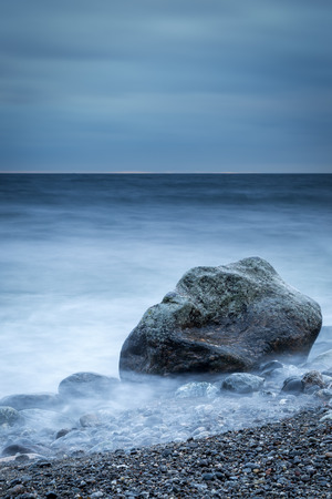 Vertical dark coastal shoreline with long exposure time Stock Photo