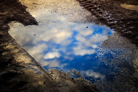 Reflection of blue sky and White Clouds in puddle on street
