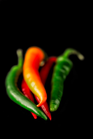 Chili pepper also known as chillies on black with selective focus and shallow depth of field photo