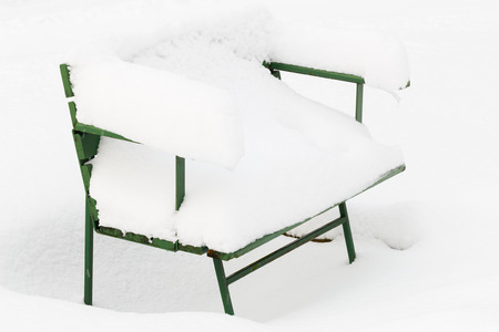 Snow-covered park bench during snowy winter after heavy snowfall