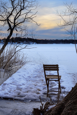 Folding chair on frozen lake during dusk twilight
