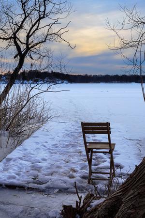 frozen lake: Folding chair on frozen lake during dusk twilight