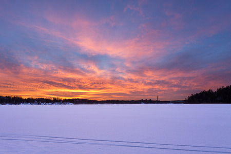 Vibrant and colorful sunset over frozen lake with ski tracks during Winter in Stockholm, Sweden
