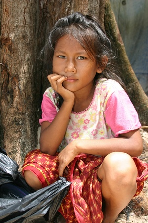Phnom Penh, Cambodia - May 15, 2005 - unidentified girl waiting by a tree, looking for anything she could salvage in her trash bag. Taken while on a missions trip to Cambodia. Children were the ones asking for money or help...  Redactioneel