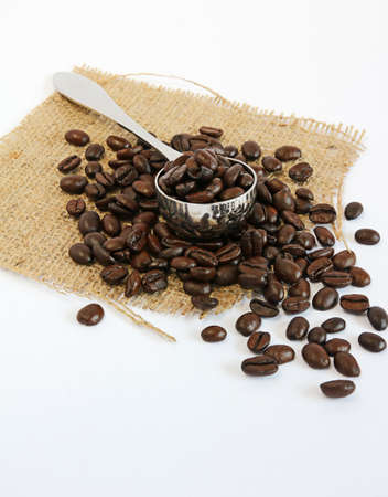 Coffee scoop filled and surrounded by coffee beans on hessian  White background with copyspace  Stock Photo - 12919048