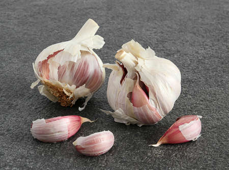 Two garlic bulbs and three cloves on a dark textured background  Stock Photo - 13001852