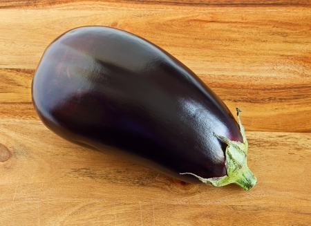 Aubergine, eggplant, on a wooden chopping board photo
