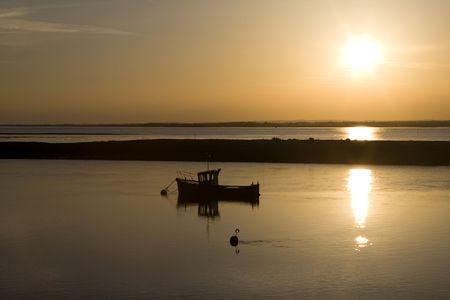 small boat during a beautiful golden sunset photo