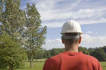 man with back to camera looking out over grass wearing a hardhat Stock Photo