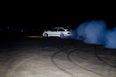 on the skids: boy race burning tyres in a car park, skids and burn outs
