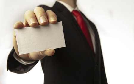 man in a suite and red tie holding a out a plain white business card for you to take  photo