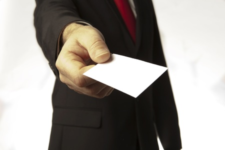 man in a suite and red tie holding a out a plain white business card for you to take