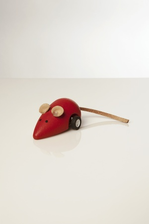 red toy mouse with wheels on white background photo