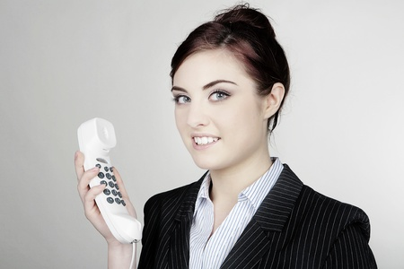 woman in business suit about to make a call on a white phone Standard-Bild